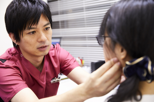 北条さんの顎を触診する高野医師